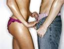 photo of a woman undoing the pants of a man