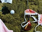 photo of a bra top lying  by a golf club and ball.