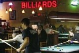 photo of men and women playing pool at a pub
