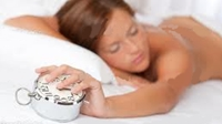 photo of a woman in bed with an alarm clock in her hand