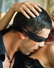 photo of a man blindfolded  with a black silk stocking for an erotic session of sex