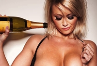 photo of a woman pouring Champagne over her breasts