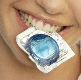 Photo of a condom in a womnan's mouth.