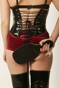 photo of a woman in a sexy corset holding a brush behind her back