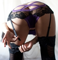 photo of a woman bending over fastening her garter