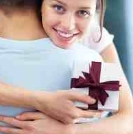 photo of a woman holding a gift behind a mans back