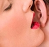 photo of a woman whispering into a mans ear
