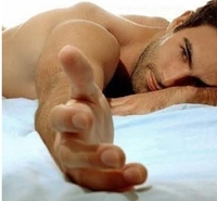 photo of a man in bed reaching forward with his hand