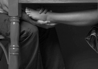 photo of a woman's bare foot under a table on a man's lap