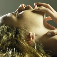 photo of a woman lying back with her eyes closed and mouth open