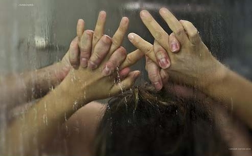 picture of the hands of a man and woman against the shower glass