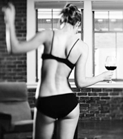 photo of a woman in bra and panties  with a glass of wine